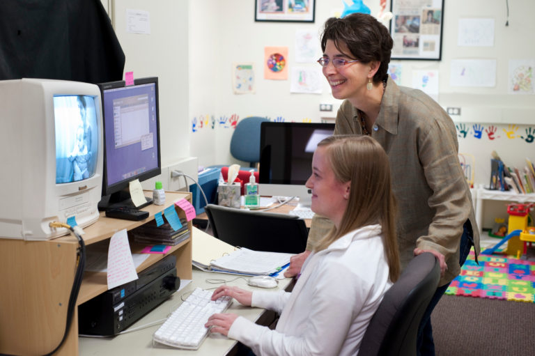 A professor and student look onto a computer monitor during a research visit in the Infant Learning Lab.